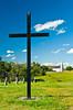 A large cross and the Church of St. Antoine de Padoue, in Batoche, Saskatchewan, Canada.