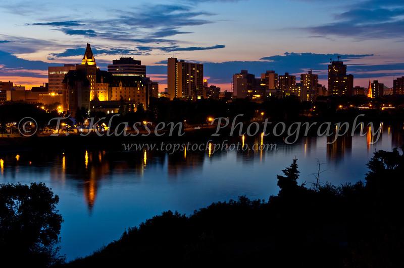 The city skyline of Saskatoon, Saskatchewan reflected in the South Saskatchewan River at dusk.