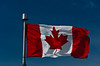 The Canadian flag with a blue sky.