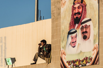 A member of the festival staff takes a break under the watchful eye of the Saud kings, past and present.