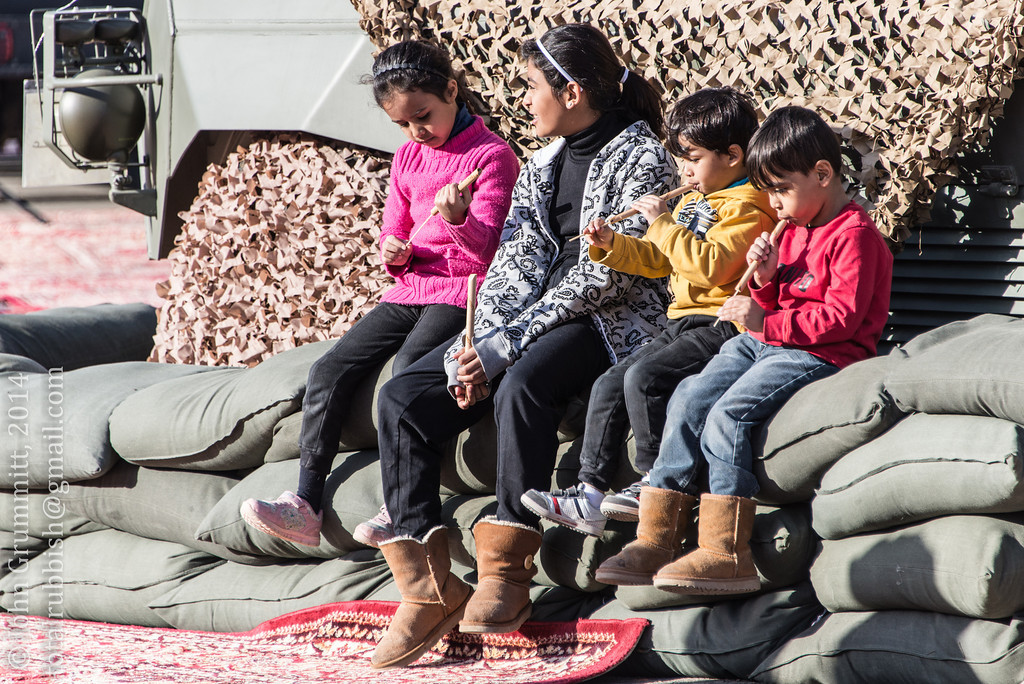 Children play with flutes while relaxing on a military display at the Department of Defense stand.