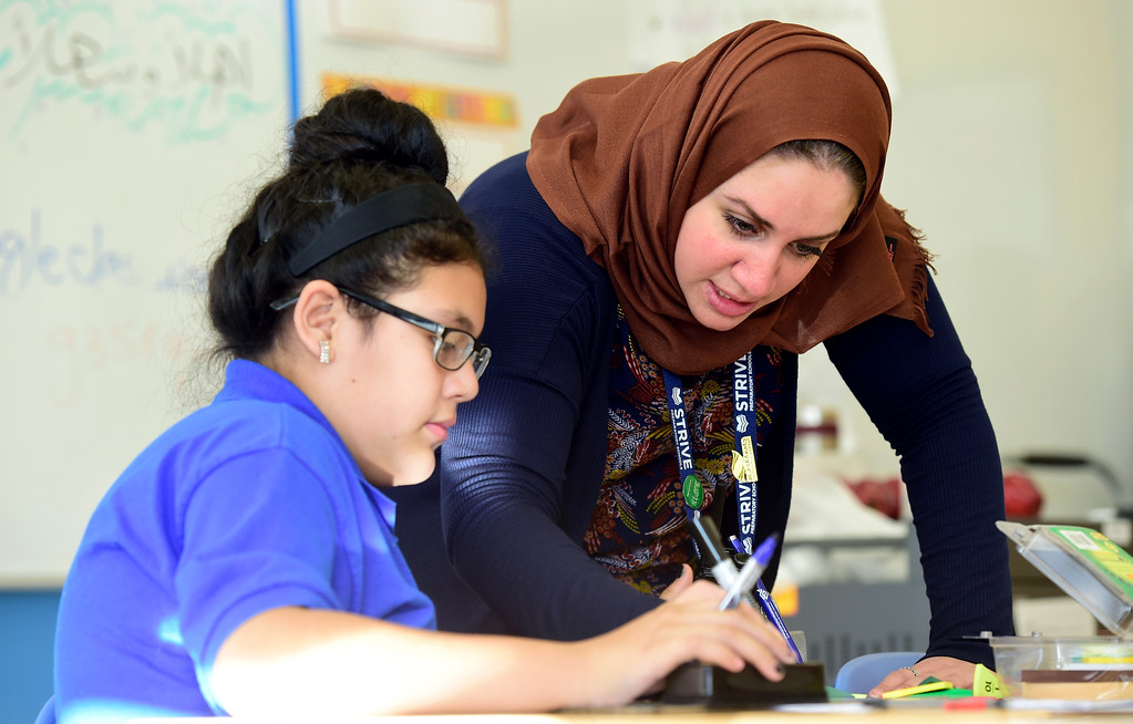 . Ms. Abu ALsamah helps sixth-grader Maria Ramirez with a match problem while teaching on Monday at the STRIVE Prep Kepner school in Denver. For more photos of Alsomah teaching at the school go to dailycamera.com Jeremy Papasso/ Staff Photographer 11/13/2017