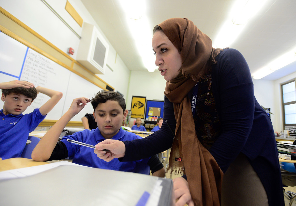 . Ms. Abu ALsamah helps Erick Rascon, left, and Danny Morales, at center, while teaching math to sixth-graders on Monday at the STRIVE Prep Kepner school in Denver. For more photos of Alsomah teaching at the school go to dailycamera.com Jeremy Papasso/ Staff Photographer 11/13/2017