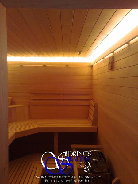 Sauna in Glenwood Springs, CO:<br /> *Hemlock paneling horizontally<br /> *Custom no-trim-molding-treatment<br /> *Low-voltage strip lighting<br /> *Standard benches in custom angles<br /> *Custom heater guard & Footrest<br /> *TV-screen<br /> *Custom corner shelf<br /> *Standard backrests
