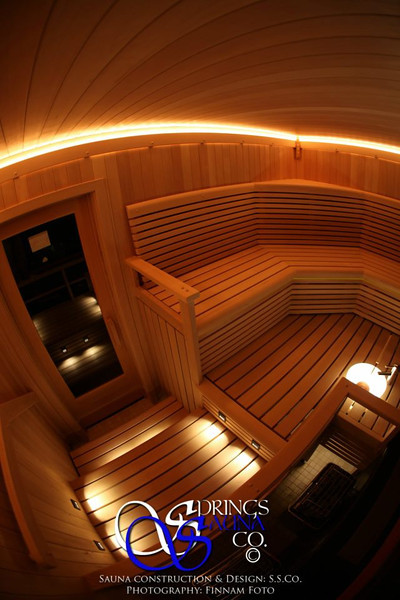 "Sauna in Saint Peters, MO (7' x 10'9"" x 8')<br /> *Western Hemlock paneling vertically<br /> *4 levels of custom built benches with rounded fascia with embedded lighting<br /> *SSC Exclusive low-voltage strip lighting along ceiling perimeter<br /> *Custom LED step lights and puck lights under sink<br /> *Hand formed crystal glass (Roc-glass) sink with faucet<br /> *Two wall-mounted stainless steel heaters<br /> *4-pane window to the outside<br /> *30"" standard clear glass door<br /> *Custom backrests, arm rests, heater guard, and corner shelf"