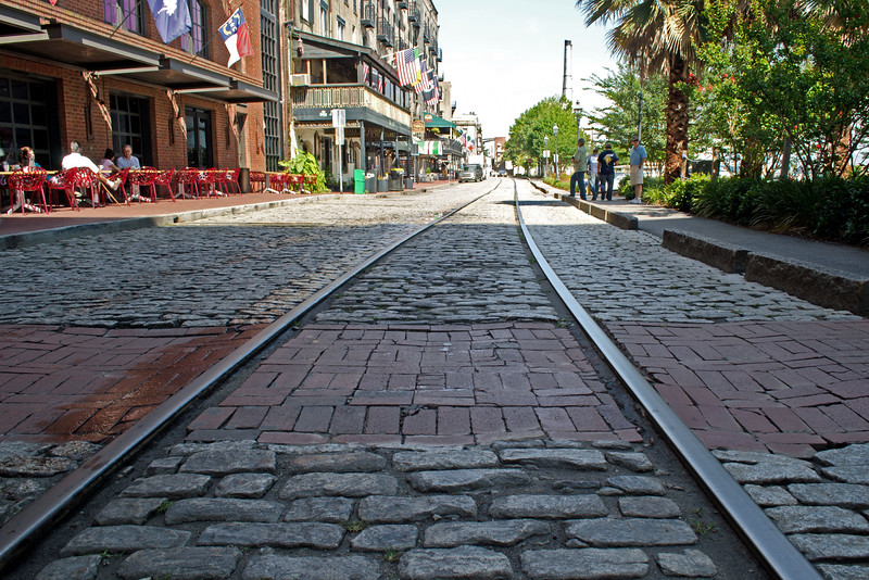 Cobblestones, bricks, and streetcar tracks along River Street in Savannah Georgia. Used as ballast in ships, the cobblestones are 200 years old. This area is the old Savannah waterfront which was used for all things cotton. Now the warehouses have been repurposed into restaurants, shops, and art galleries.
