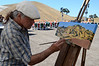 Painter Greg Piatt puts finishing touches on his live auction item, a plein air oil painting of the mountain.