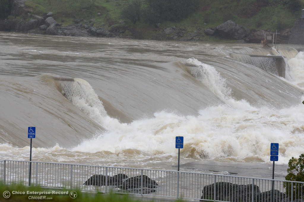 . Water pours Saturday, Feb. 18, 2017, over the Fish Barrier Dam into the Feather River near the Feather River Fish Hatchery in Oroville, California, after the broken Oroville Dam spillway sent dirt and debris into the Diversion Pool and Feather River, threatening the fish at the hatchery. (Dan Reidel -- Enterprise-Record)