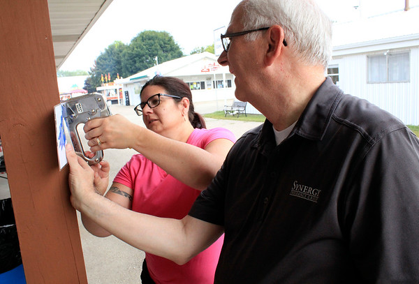 Roger Schneider | The Goshen News<br /> Jen Fisher of Nappanee and Phil Evans, Goshen, post signs Friday at the Kiwanis ribeye steak booth.