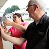 Roger Schneider | The Goshen News<br /> Jen Fisher of Nappanee and Phil Evans, Goshen, post signs Friday at the Kiwanis ribeye steak booth.