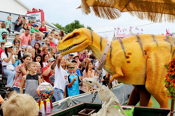 CAMDEN CHAFFEE | THE GOSHEN NEWS<br /> A remote-controlled T. Rex interacts with the crowd during the Jurassic Kingdom show Monday at the Elkhart County 4-H Fair.
