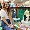 AIMEE AMBROSE | THE GOSHEN NEWS <br /> Grace Caffee, 17, Middlebury, kneels next to her Disney princess-themed cake, which won a reserve grand champion ribbon in the 4-H exhibit hall at the Elkhart County Fair.