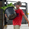 BEN MIKESELL | THE GOSHEN NEWS<br /> Wyatt Erb, 13, of Milford, decorates the exterior of the swine club Thursday at the Elkhart County 4-H Fairgrounds.