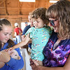 BEN MIKESELL | THE GOSHEN NEWS<br /> Eloise Prahl, 3, of Elkhart, pets a piglet born July 20 with her mother Jessica while at the Young McDonald barn.