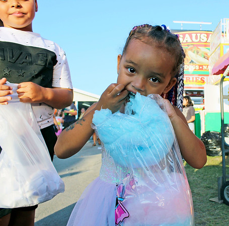 CAMDEN CHAFFEE | THE GOSHEN NEWS<br /> Keeley Harris eats her snack of cotton candy as she walks with her family Wednesday at the Elkhart County 4-H Fair.