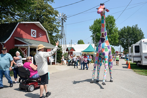 BEN MIKESELL | THE GOSHEN NEWS<br /> Skittles the Giraffe greets fairgoers Tuesday.