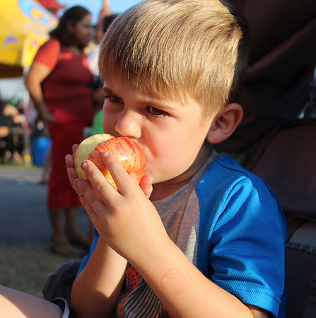 CAMDEN CHAFFEE | THE GOSHEN NEWS<br /> Elijah Shipe eats an apple while waiting to go on the carousel Wednesday at the Elkhart County 4-H Fair.
