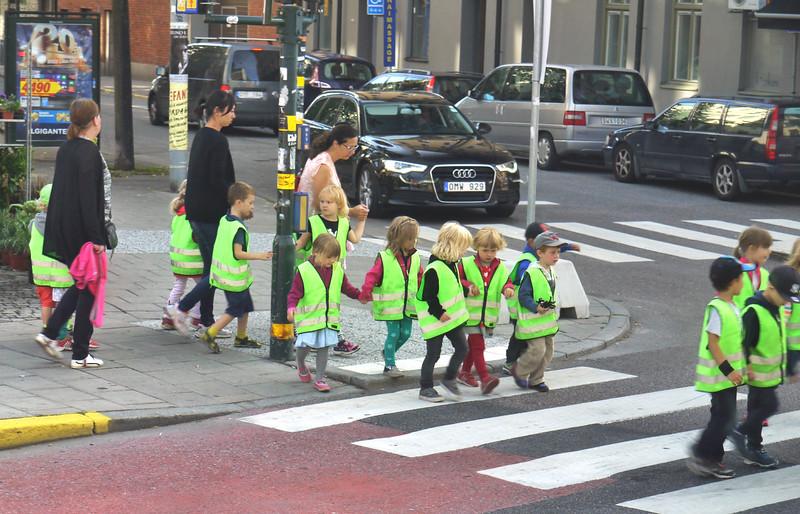 School children wearing vests in city streets.