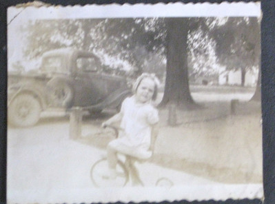 Mom on a bike, look at that old truck in the back!