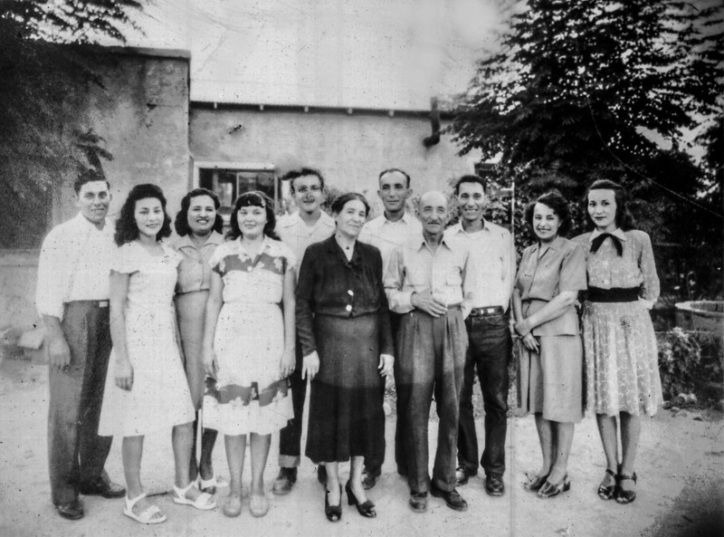 Sort ID: 1947-01 Image ID: C122 (est) Year: 1947  Photo content: The Ortega's in Florence: left to right: Bert, Carmela, Sara (mother), Caroline (aka Tootsie), Joe Louis, Sara (the matriarch), Fernando, Fernando Sr, Victor, Mary, Josephine. Not in the picture: Teresa (maybe she took the photo) and Elias who had died of meningitis in the Army in 1942. The photo was taken after 1945 and before 1949 as Fernando Sr is present and Victor, Fernando, Bert are present (and likely discharged from their war-time military service.) The home is the family residence on 6th Street in Florence before the move to the home located at the intersection of E 8th street and N Pinal Street in Florence, in the same block as the Catholic Church. The 1940 US Census shows the Ortega's living on 6th Street in Florence with no house number.