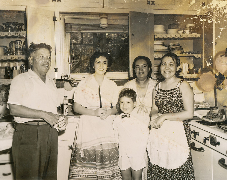 Sort ID: 1955-01 Image ID: B018  Year: July 1955. Photo content: Dad, Christina Gabusi, Fred, mother, Teresa; after Michael's baptism; note the fried chicken on the Chambers stove. Location of photo: 1231 E. Edison, Tucson.