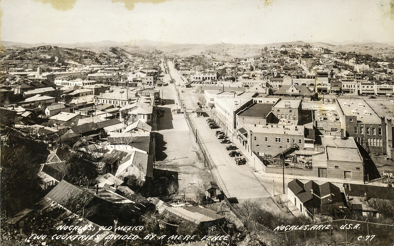 """Sort ID: 1937-01 Image ID: C390 Year: 1937.  Photo content: Vista of the border at Logales, facing west, showing Nogales, Mexico on the left, and Nogales, AZ on the right. """"Two countries divided by a mere fence."""""""