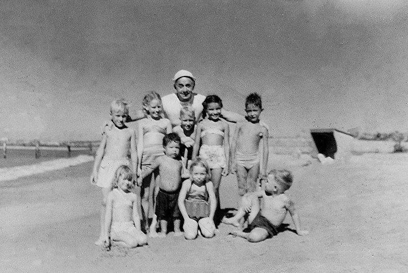 Sort ID: 1951-V06A Image ID: C563 (est) Year: 1951. Margaret, Edward, Fred with other children in Cardon, Venezuela. Adult is Mr Bilyk. Print was stamped June 11, 1951 by film processing lab.