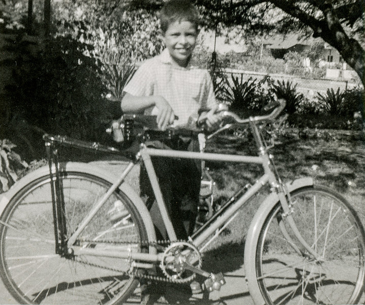 Sort ID: 1955-Dec  Image ID: B559 (est) Year: 1955. Fred on Christmas Day 1955 standing with his first real bicycle in Cardon, Venezuela. Moments after this photo, Fred rode off on to the street and decided it would be interesting to put both feet on the handlebars. He crashed immediately. Scars on his left hand from that adventure lasted for decades.