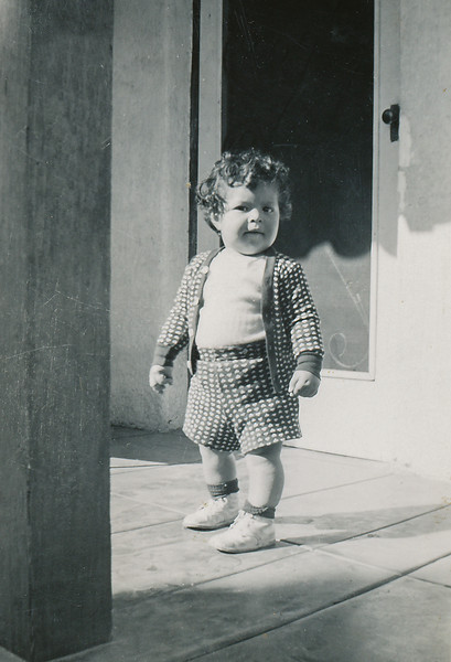 """Sort ID: 1950-A01 Image ID: C588 (est) Year: 1950.  Fred in front of 1231 E Edison St, Tucson. Mother's inscription: """"Here you are in miniature. Do you see how he's built like you. This is the one I like best."""""""