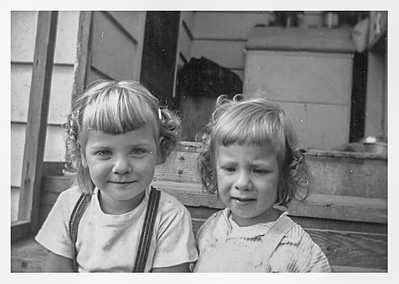 Mom's attempt at curling our hair.  Mine never lasted the day. I also like this picture because of the woodbox on the porch in the background.  It was our job to carry the wood from that box into another smaller box beside the  wood stove.  Our cat, Suzie, often chose to have her kittens in this woodbox too.  You can see Suzie's food and water dish by the woodbox.  This is where Mom stood when she hung out clothes on the reeled clothes line.