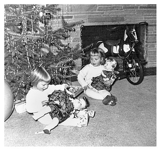 This is probably December 54.  We and the Canfield girls all got similar dolls.  Mom made doll clothes for all of them.  I had pleaded for a horse, so Dad found this horse tricycle for us.