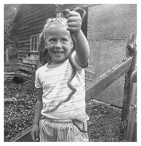 Linda with a garden snake.  We used to have lots of fun catching and playing with these.  They ate the slugs that ate Mom's garden, so she was happy to have them around.