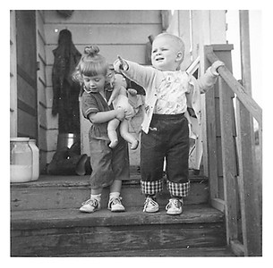 "Brent Gelaude and Jenny on the porch.  I especially remember those gallon jars of milk from our cow, Brownie.  It was unpasteurized, so the cream floated to the top. Mom would make our own butter from it.  One of our neighbor's, Mrs. Ward, bought what we couldn't use ourselves.  Linda and I used to carry it to her in those jars. ""Don't drop it, and don't spill it."""