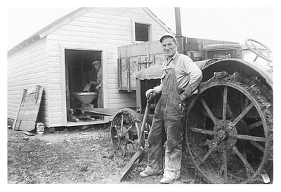 The hired hand by the tractor. The soil became very sticky when wet. It clung to the tractor wheels and even to your shoes, in big clumps.   Grandpa can be seen in the shed.