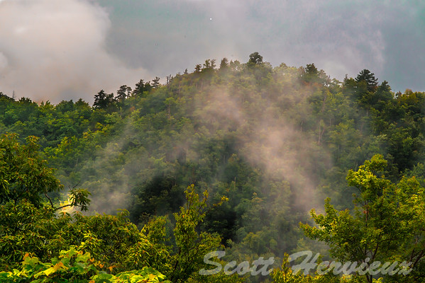 The mountains in western North Carolina are known as the smokey mountains (also known as the blue ridge mountains).  Reason is the clouds and fog give it a blueish color, and the fog rising up looks like smoke.