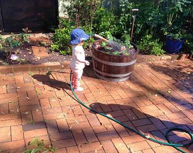 Scarlett watering Nanna's garden - Age 18 Months