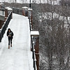 A student makes her way across the footbridge after a recent snow.
