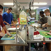 Journalist and author David Hanson '00 (left) working with students at the Campus Kitchen.