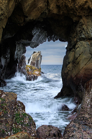 A cave, a rock and the ocean