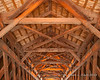 Looking up at the roof structure of the bridge.  This bridge has three lights in the roof at equal distances to help people traveling through
