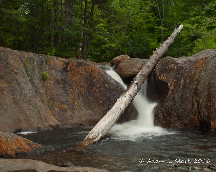 The uppermost cascade with a log in the stream