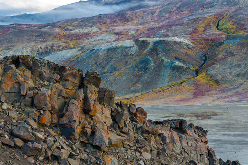 9/12/15, 8:28 AM. A rocky outcrop with orange leichen against the colorful tundra of the mountains in the background.