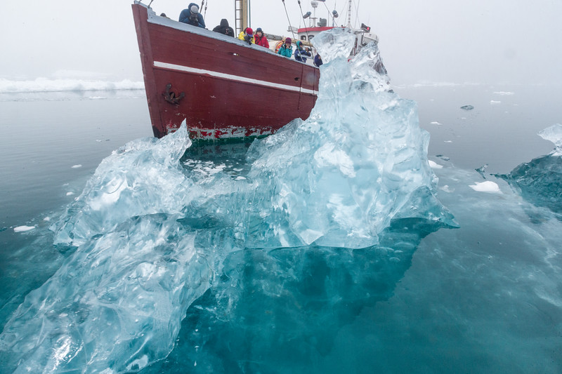 Powerboat appears to be crashing through the clear iceberg, but it's an optical illusion.
