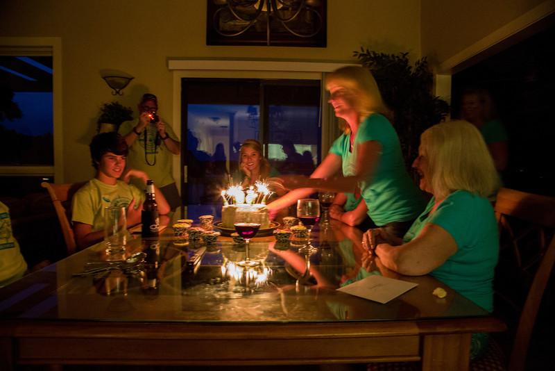 Nick, Charlie (camera),  Sam, Dana (hidden) and Linda watch Debbie set the red velvet anniversary cake down with sparkler candles providing the light.