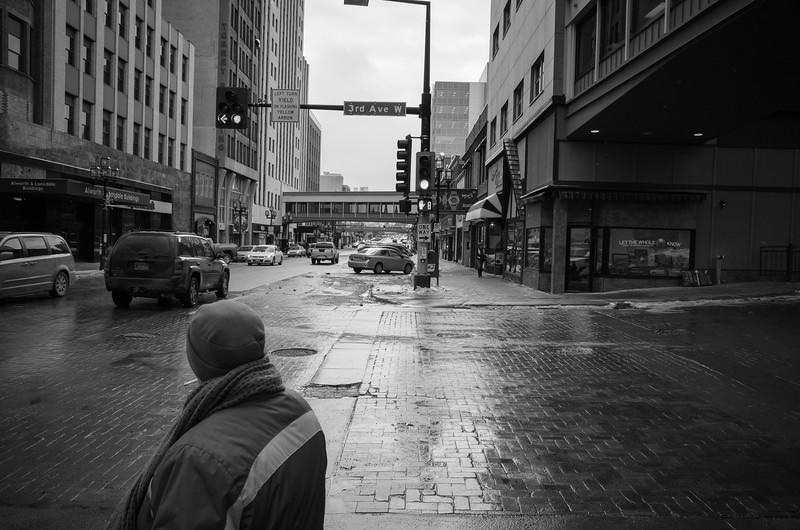 A smoking man crosses the street