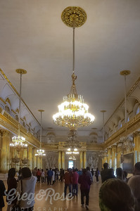 Chandeliers an gold and mirrors and windows, light dominates