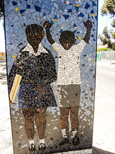 The boy hands held high and the girl in school clothes represents the terror and death that occurred during the apartheid regime