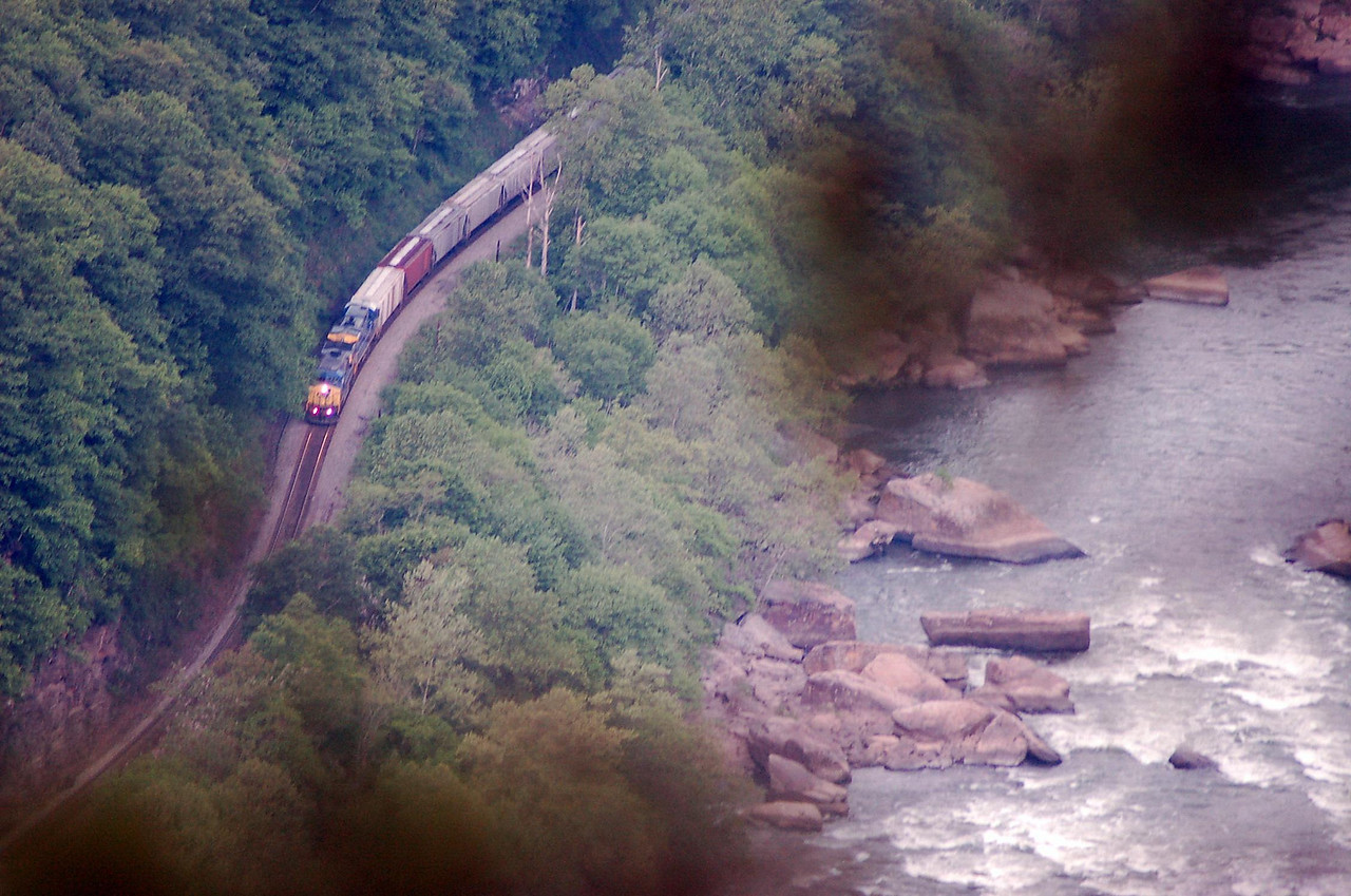 A southbound CSX train on the west side of the river.<br /> Compare the size of the rocks in the New River and the railroad engine.<br />    This shot was taken through trees while hanging over a (very) high ledge.