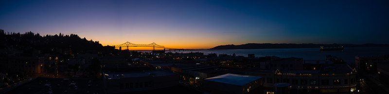 The Astoria-Megler Bridge connecting Oregon and Washington and the city of Astoria, OR at sunset from the roof of the Hotel Elliott.