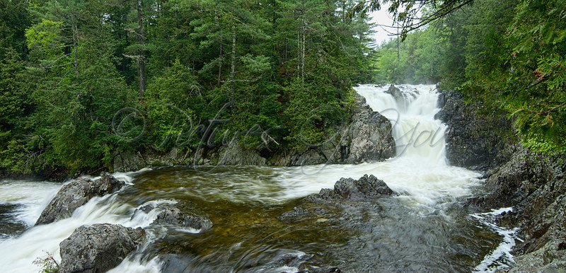 Split Rock Falls Pano, New Russia<br /> <br /> Description of the Falls:<br /> <br /> The Split Rock Falls in the Adirondack Park is a very popular and pretty spot. The falls get very strong and powerful in high water after heavy rainfall. The water is clear and cold as it cascades through natural steps made of granite and slate.  There  are two drops, the first about 30 feet in height, and the other plunges about 40 feet with a mid-level pool in-between.  The pool at the bottom of the lower cascade is estimated to be about 8 feet deep, making it a popular jumping spot from the top of the ravine.  Hemlock and Spruce trees line the ravine, and trout fisherman sometimes get lucky.  The falls are part of the Boquet River located on NY state-owned land.  The Boquet River is among the steepest rivers in NY starting as just two streams high up in the Dix Mountain Range and converge just ahead of the falls.<br /> <br /> <br /> <br /> Directions to the Falls:<br /> <br /> Split Rock Falls is one of the easiest waterfalls to reach since it is just a few steps from the road, making it a popular swimming spot.  It's location is not marked and can be found on NY Route 9 following the Boquet River.  From exit 30 on the Adirondack Northway (I-87) go northwest on NY Route 9/73 toward Lake Placid for approx 2.4 miles until you come to a large intersection. Take a right to continue north on Rte 9.  You will drive over a small bridge crossing the Boquet River just above Split Rock Falls. This point is 2.3 miles from route 73 and 4.7 miles from I-87. There is a small, unmarked parking area on the right side of the road just past the bridge.  In the summer, the lot can fill up quickly with swimmers and jumpers. Be cautious, several people have drowned through the years at this location.  Protective fences used to line the ravine, but swimmers have been quick to tear them down.  Be sure to explore great photo ops from a variety of locations along the river's ravine being careful not to slip.  Unless the water is flowing heavily, make your way to the bottom to swim or take additional photos.